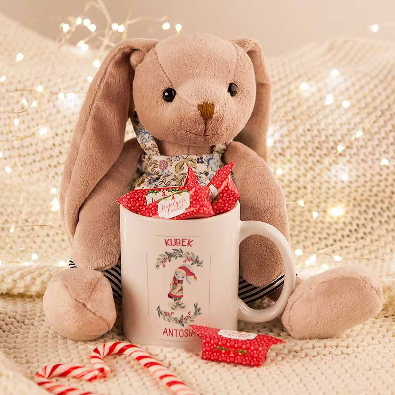 Prezent świąteczny dla dziecka z maskotką, kubkiem i słodkimi krówkami