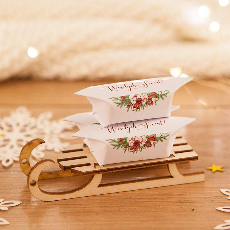 Świąteczny słodki upominek krówki na sankach z napisem Wesołych Świąt