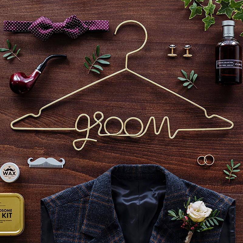 Metalowy wieszak w złotym kolorze z napisem Groom